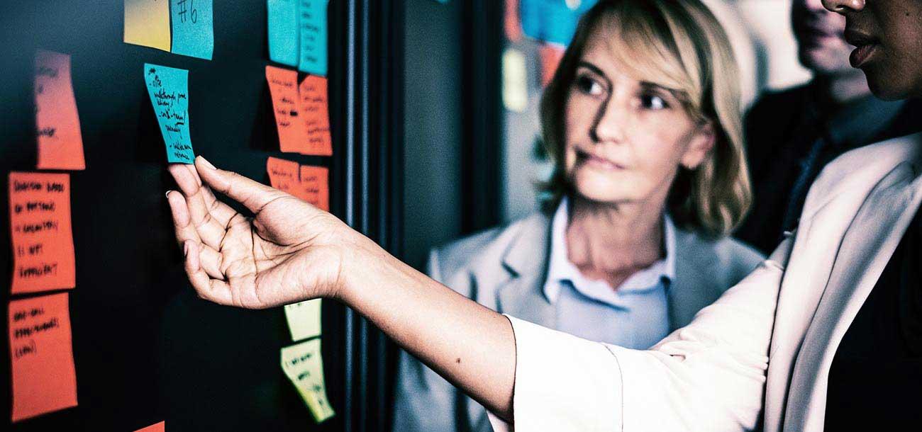 employees-brainstorming-marketing-tactics-on-bulletin-board