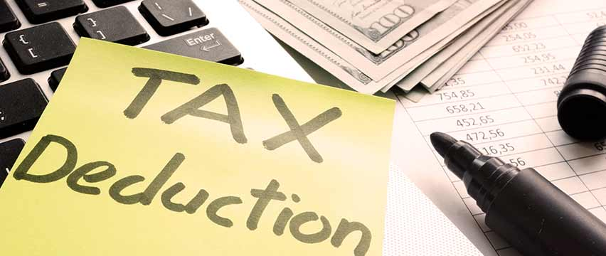 Section 179 tax deduction documents on top of a calculator and spreadsheet