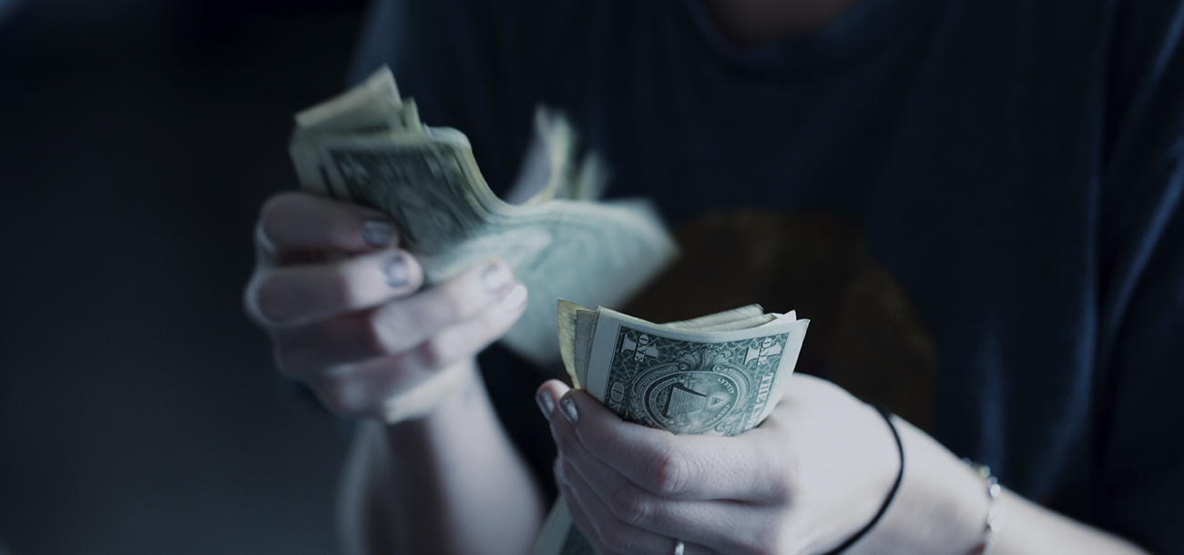 Close up of woman's hand counting cash for small business loans